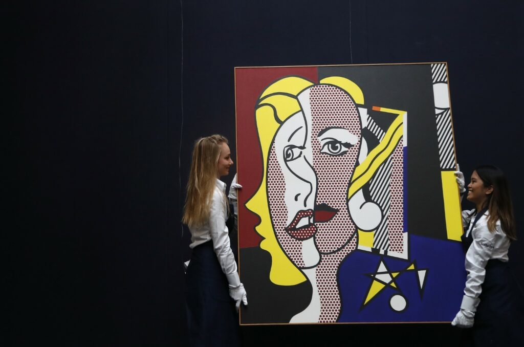 Sotheby employees adjust the oil and magna on canvas painting, Female Head by Roy Lichtenstein at Sotheby's auction house in London, Friday, Oct. 6, 2017 ahead of New York sales for Contemporary, Impressionist & Modern Art by Monet, Cèzanne, Miró, Magritte, Picasso, Basquiat, Dubuffet & Lichtenstein. The painting is estimated to fetch US$10-15 million . (AP Photo/Frank Augstein)