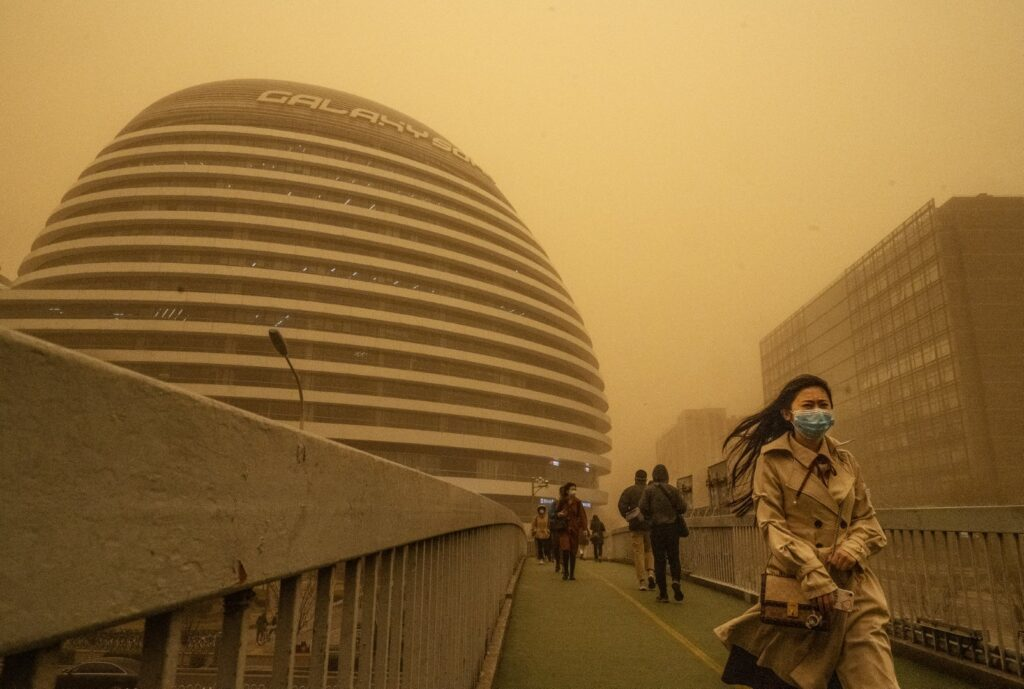 BEIJING, CHINA - MARCH 15: People wear protective masks as they commute during a sandstorm on March 15, 2021 in Beijing, China. China's capital and the northern part of the country was hit with a sandstorm Monday, sending air quality indexes of PM 2.5 and PM 10 ratings into the thousands and cancelling flights. (Photo by Kevin Frayer/Getty Images)