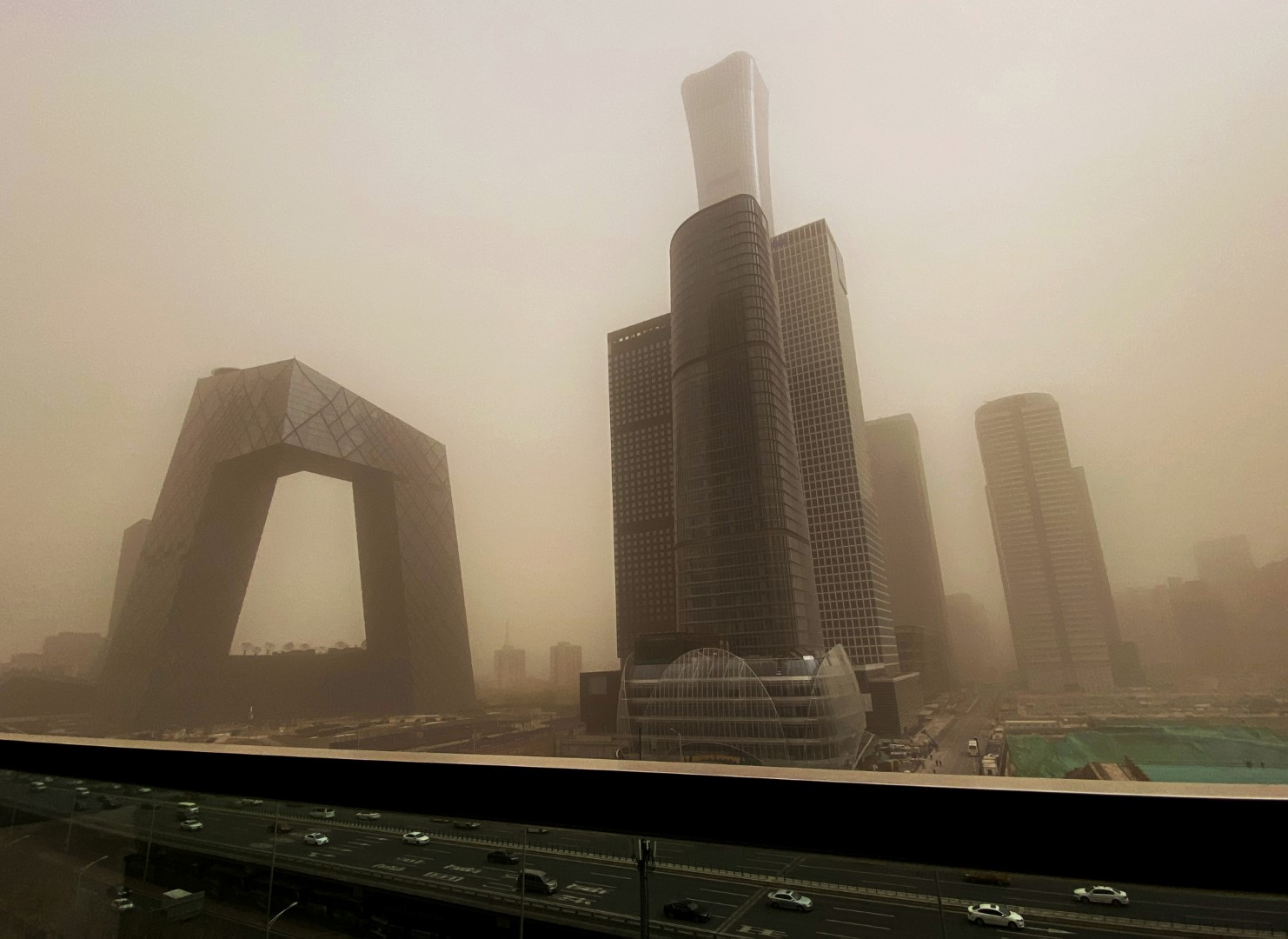 BEIJING, CHINA - MARCH 15: The CCTV building and the Central Business District is seen shrouded in air pollution during a sandstorm on March 15, 2021 in Beijing,