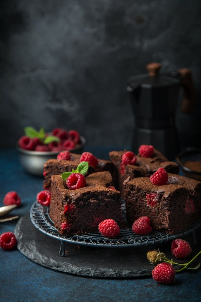 raspberry brownies served with fresh berries, dark background, selective focus