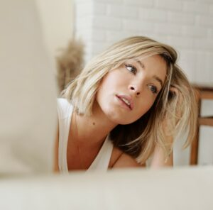blonde woman looking in a mirror