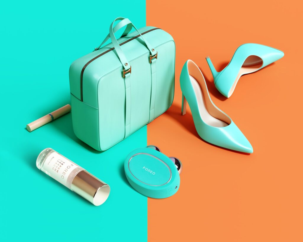 Woman's accessories bag, high heels, lipsticks on blue and orange background. 3d rendering