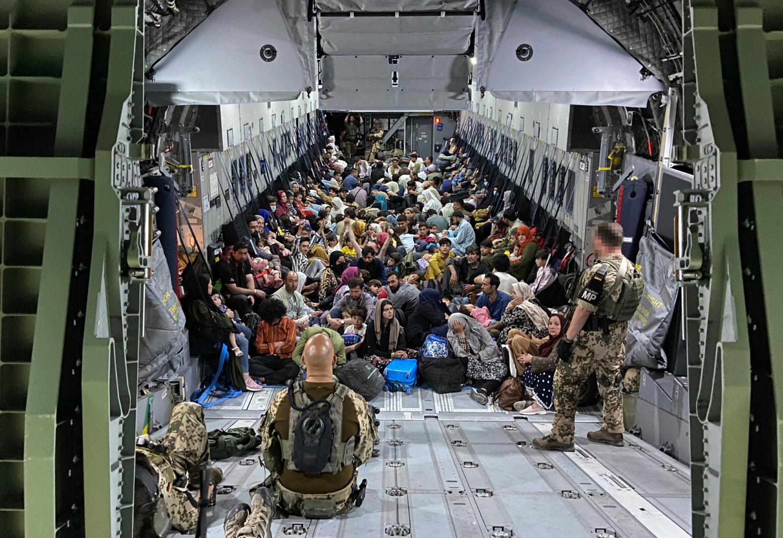 TASHKENT, UZBEKISTAN - AUGUST 22: In this handout image provided by the Bundeswehr, evacuees from Kabul sit inside a military aircraft as they arrive at Tashkent Airport on August 22, 2021 in Tashkent, Uzbekistan. German Chancellor Merkel said Germany must urgently evacuate up to 10,000 people from Afghanistan for which it is responsible. (Photo by Handout/Bundeswehr via Getty Images)