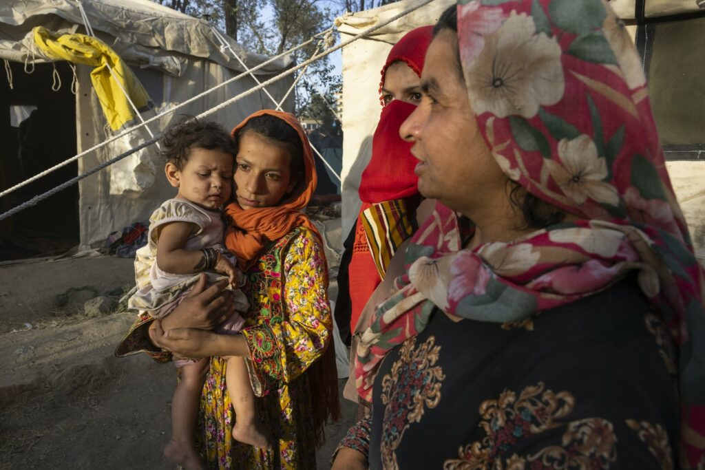 KABUL, AFGHANISTAN - AUGUST 10: Halida ,11, from Tahar, who lost her father, killed by the Taliban holds her cousin Shafika, 8 months, along side family as displaced Afghans arrive at a makeshift camp from the northern provinces desperately leaving their homes behind on August 10, 2021 in Kabul, Afghanistan. The Taliban has taken control of six provincial capitals, among other towns and trade routes, since the United States accelerated withdrawal of its forces this year. Afghan families from Kunduz, Takhar and Baghlan provinces have arrived in Kabul in greater numbers, fleeing the Taliban advance. (Photo by Paula Bronstein /Getty Images)
